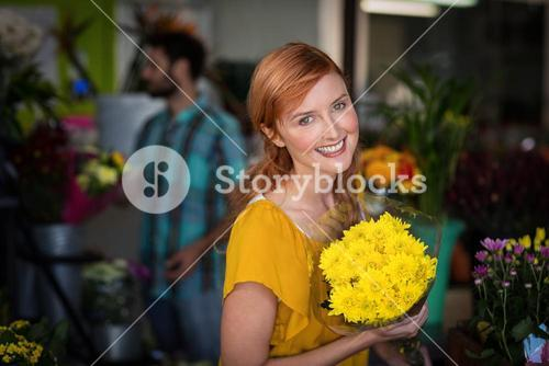 Portrait of female florist holding bouquet of flower