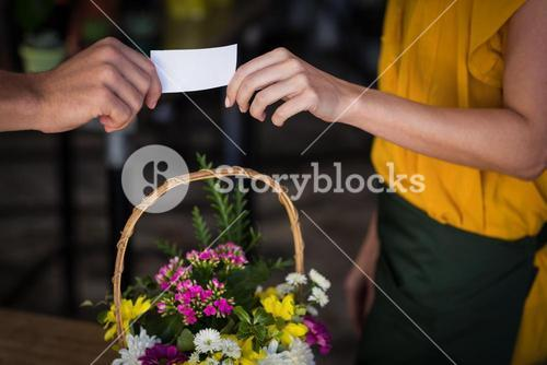 Female florist giving visiting card to customer