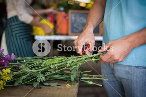 Male florist preparing flower bouquet