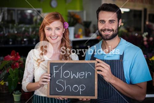 Portrait of couple holding slate with flower shop sign