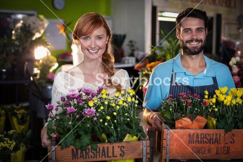 Portrait of couple holding crate of flower bouquet