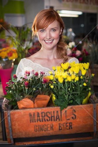 Female florist holding crate of flower bouquet