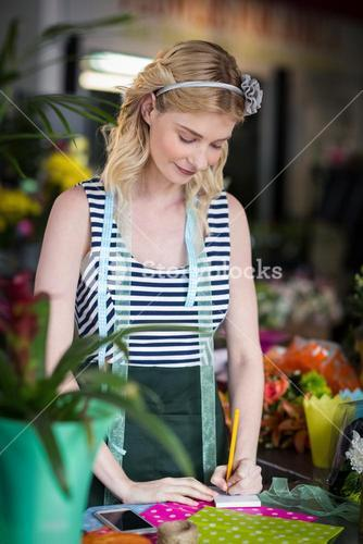 Female florist writing on a notepad