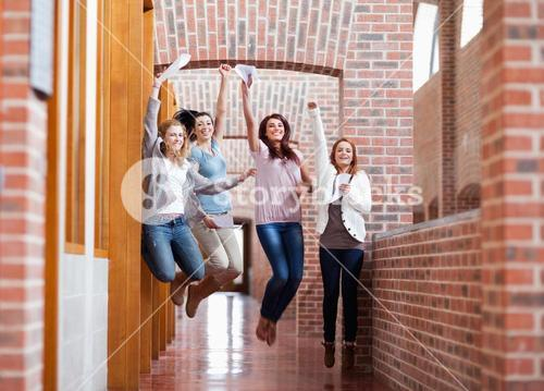 Students jumping with their results
