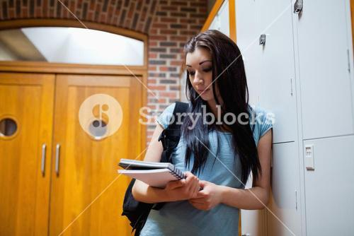 Studious young woman reading her notes