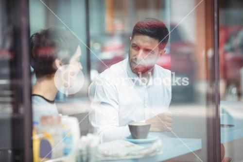 Businesspeople interacting while having coffee