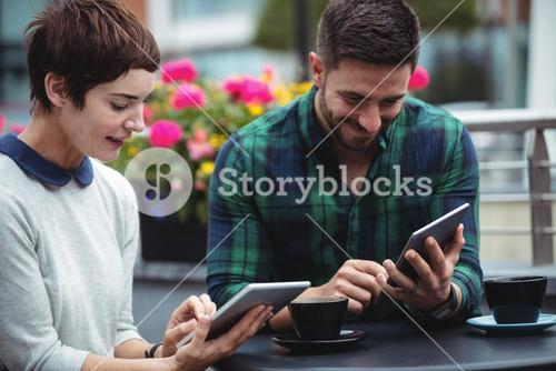 Businesspeople using digital tablet while having coffee