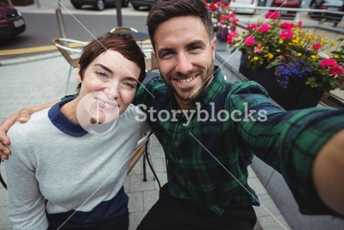 Couple posing for selfie in cafeteria