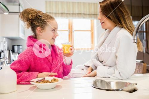 Mother and daughter interacting with each other in kitchen