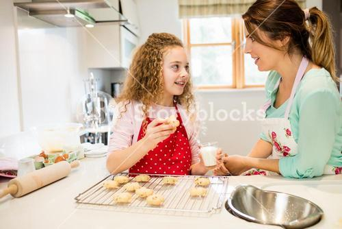 Daughter interacting with mother while having cookies in the kitchen