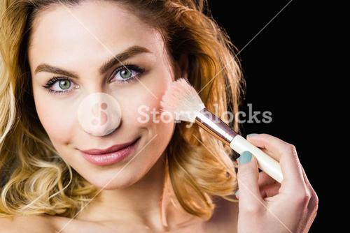 Portrait of beautiful woman posing with make-up brush
