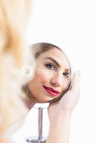 Reflection of beautiful woman in hand mirror