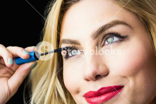 Beautiful woman applying mascara on eyelashes against black background