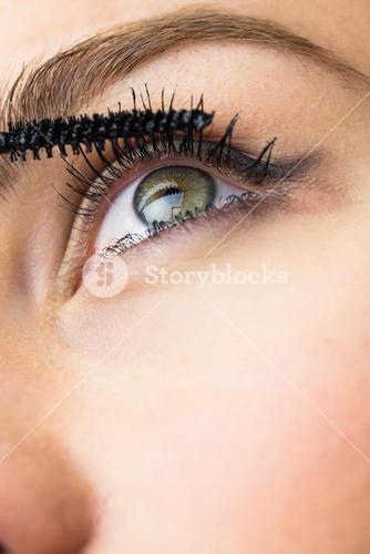Beautiful woman applying mascara on eyelashes
