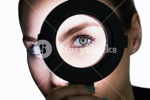 Close-up of beautiful woman in hand mirror