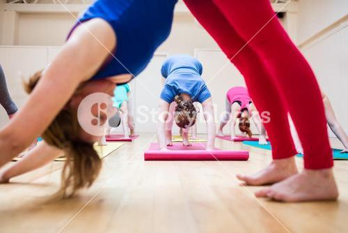 Trainer assisting group of people with downward dog yoga exercise