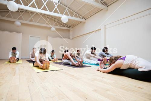 Trainer assisting group of people with pashimottanasana exercise