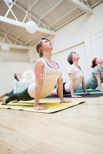 Group of people performing cobra pose on exercise mat