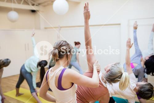 Trainer assisting group of people with stretching exercise