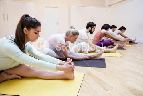 Group of people performing stretching exercise on exercise mat