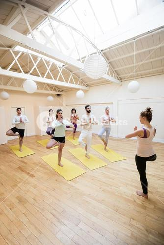 Trainer assisting group of people with tree pose exercise
