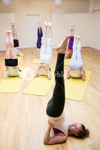 Trainer assisting group of people with sarvangasana exercise
