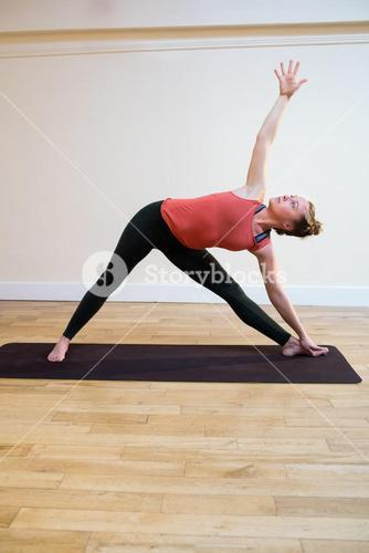 Woman performing triangle pose on exercise mat