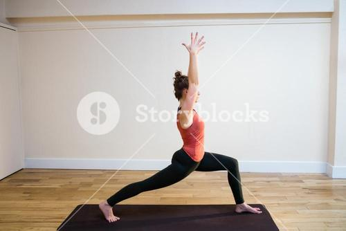 Woman performing warrior pose on exercise mat