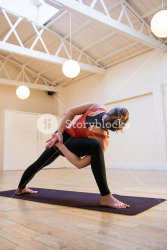 Woman performing bound side angle pose on exercise mat