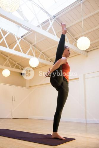Woman performing bird of paradise yoga pose on exercise mat