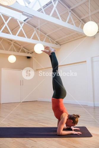 Woman performing handstand pose on exercise mat