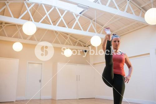 Woman performing stretching exercise on exercise mat