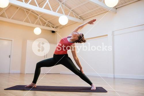 Woman performing extended side angle pose on exercise mat