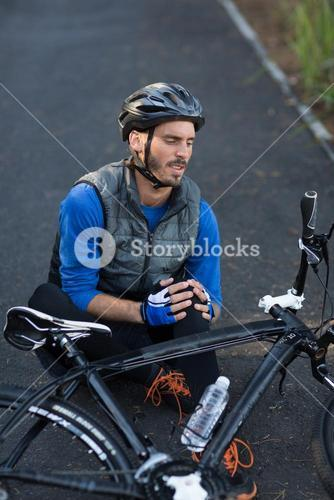 Male biker in pain holding his injured leg