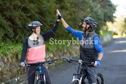 Biker couple giving high five while riding bicycle on the road