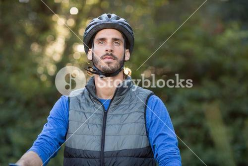 Thoughtful male biker in forest