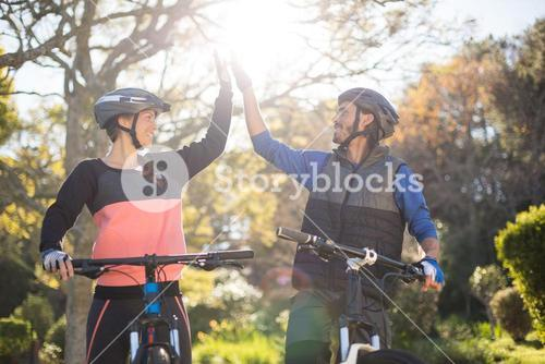 Biker couple giving high five while riding bicycle in countryside