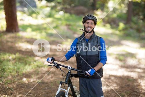 Male biker standing with mountain bike in forest