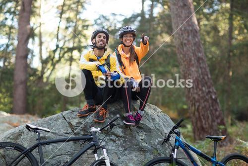 Biker couple sitting on rock and pointing in distance