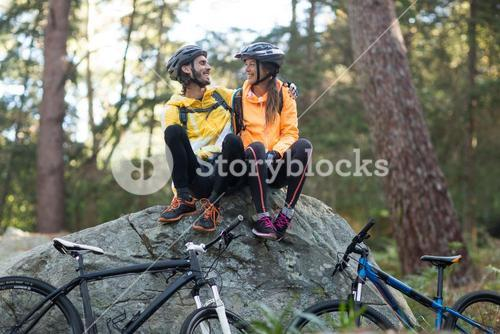 Biker couple sitting on rock and interacting with each other