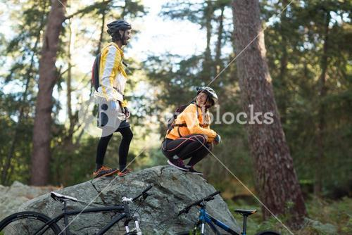 Biker couple interacting with each other in forest