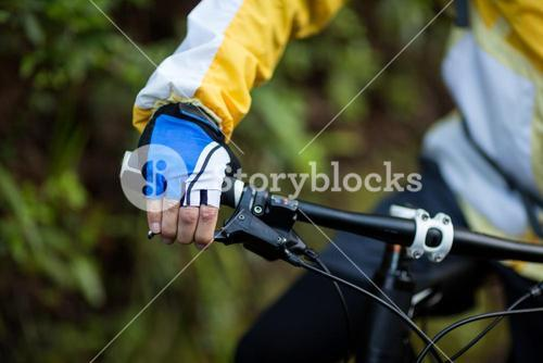 Mid-section of male biker with mountain bike