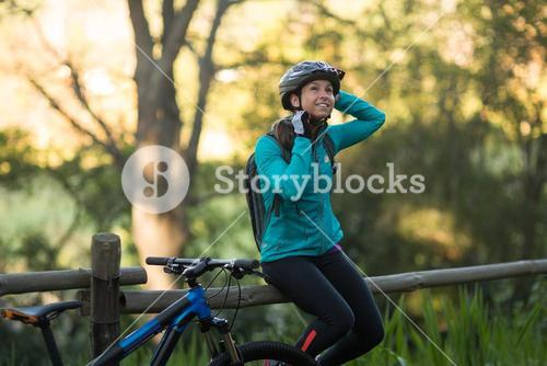 Female biker sitting on a fence and removing bicycle helmet