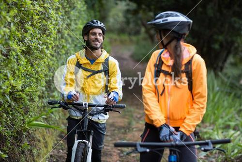 Biker couple interacting while cycling in countryside