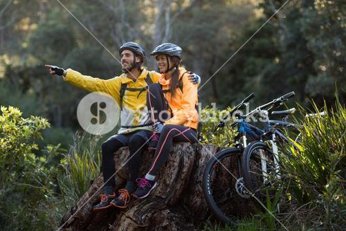Biker couple sitting and pointing in distance