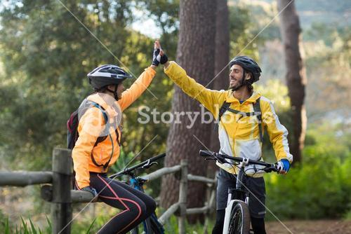 Biker couple giving high five to each other in countryside