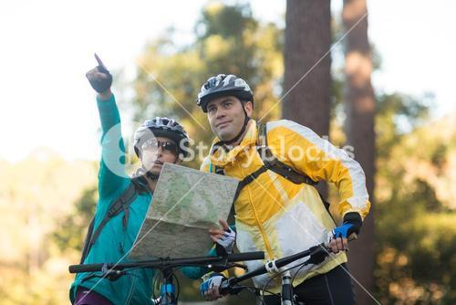 Biker couple with a map pointing in distance