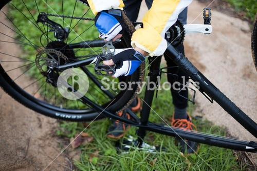 Low section of male biker repairing mountain bike