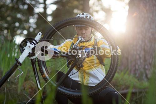 Male biker repairing mountain bike