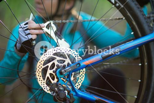 Mid-section of female biker repairing mountain bike